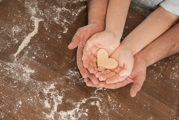 Dough heart shape in father and son hands Premium Photo