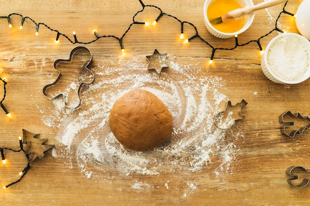 Dough near forms for biscuits and fairy lights Free Photo