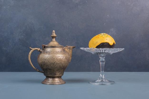 古代のやかんとガラスプレート上のドーナツ。 無料写真