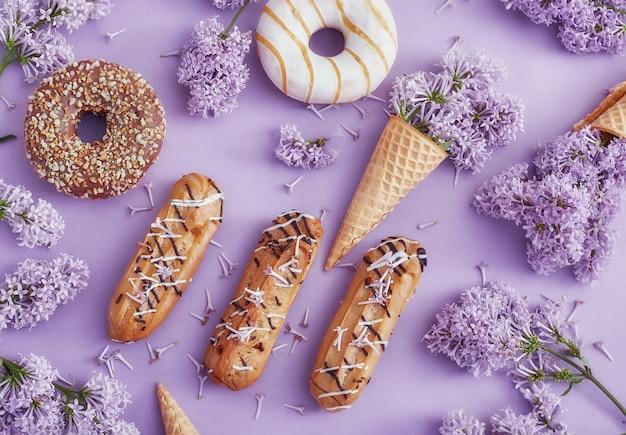 Пончики и пирожные с кремом лежат на столе среди сиреневых цветов на фиолетовой бумаге. весна и сладости, вкусные пирожные. натюрморт и летнее настроение, вид сверху. пончики Premium Фотографии