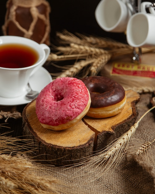 Doughnuts with red and chocolate cream and a cup of tea. Free Photo