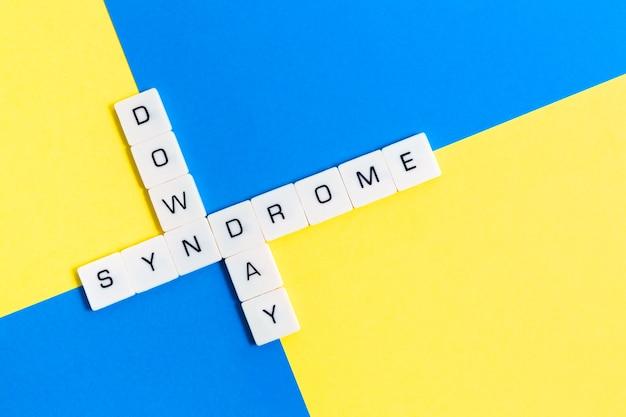 黄色と青の背景に分離されたクロスワード文字で「ダウン症の日」メッセージ。 Premium写真