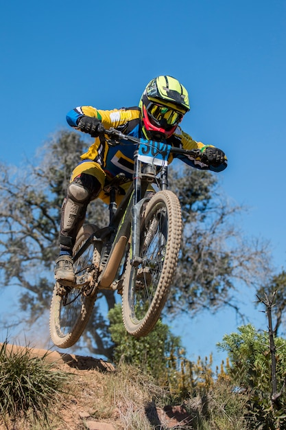 Downhill competition, biker jumps fast in the countryside. Premium Photo