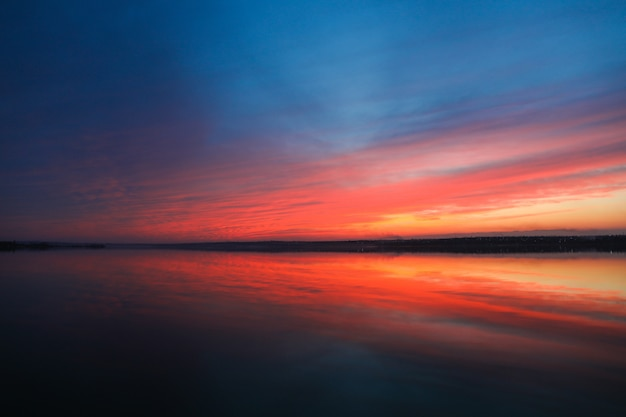 Dramatic sunset sky background with river, fiery clouds, yellow, orange and pink colour, nature background. beautiful skies Premium Photo