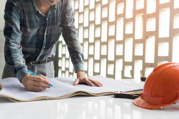 エンジニアとセキュリティヘルメットは、青写真紙drawinを見て建設計画を説明しています Premium写真