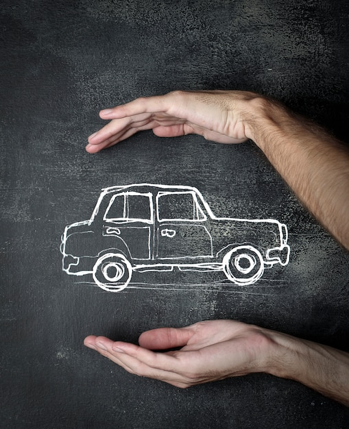 Drawing of a car between hands Premium Photo