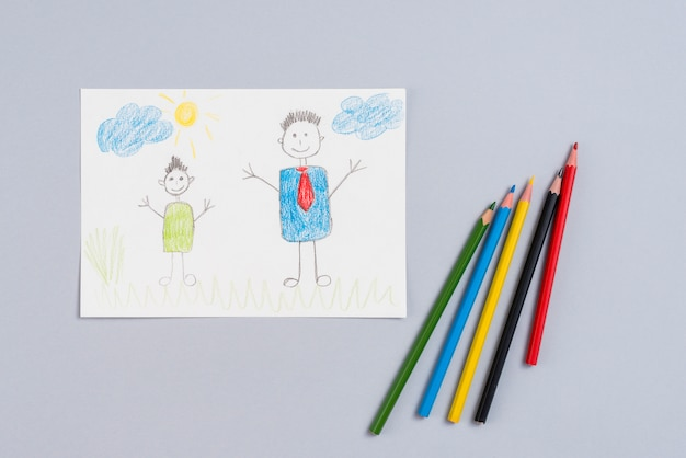 Drawing of father and son on paper with pencils Free Photo