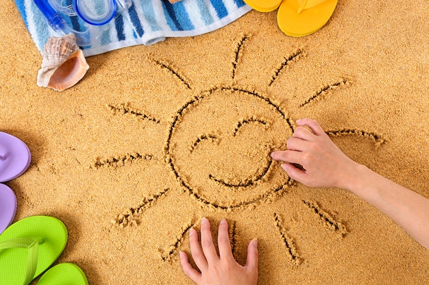 Drawing a happy sun on the beach Free Photo