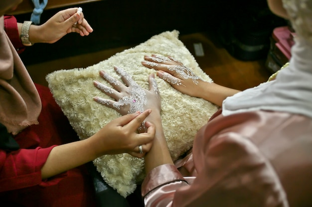 Drawing mehndi or henna on bride hands Premium Photo