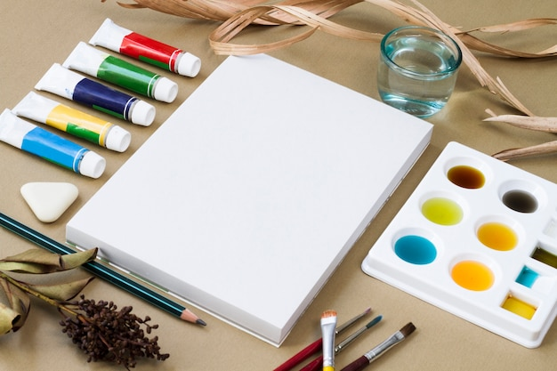 Drawing supplies located around canvas Free Photo