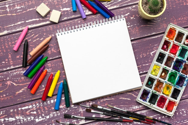 Drawing tools, supplies, workplace of artist. watercolor paints and blank notepad on  wooden desk Premium Photo