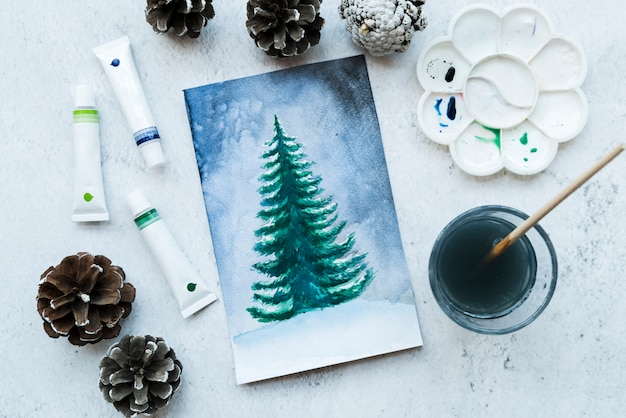 Drawn christmas tree canvas with pinecones; color tubes and paint brush on textured backdrop Free Photo