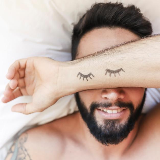 Drawn eyelashes on man's hand sleeping over bed Free Photo