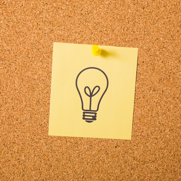 Drawn light bulb on adhesive note attached with pushpin on notice board Free Photo