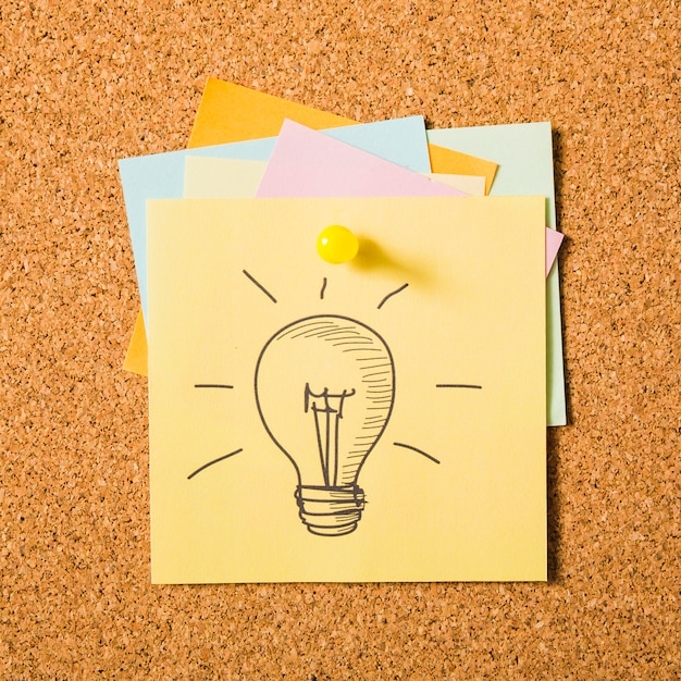 Drawn light bulb icon on adhesive note attached with pushpin Free Photo