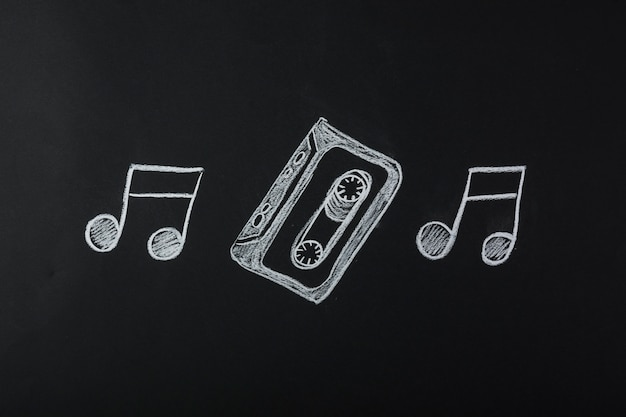 Drawn musical notes with cassette tape on blackboard Free Photo