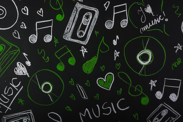 Drawn musical notes with cassette tape; compact disc on blackboard Free Photo