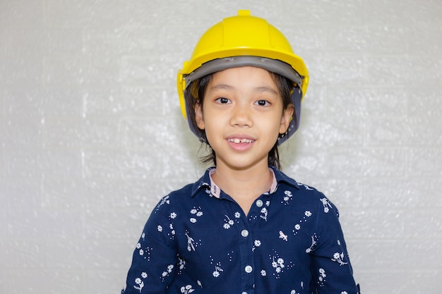 Dream career concept, portrait of happy engineer kid in hard hat looking at camera on blurred background Premium Photo
