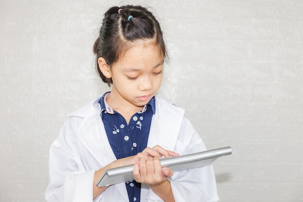 Dream careers concept, little kid girl doctor typing at wireless computer keyboard, portrait of happy child in doctor coat with blurred background Premium Photo
