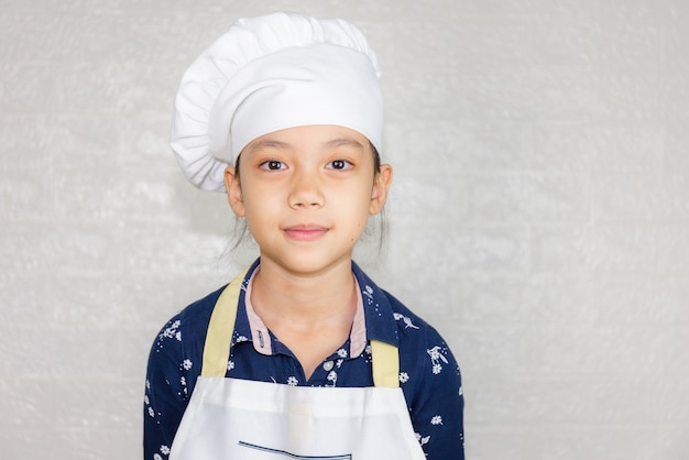 Dream careers concept, portrait of happy kid chef looking at camera with blurred background Premium Photo