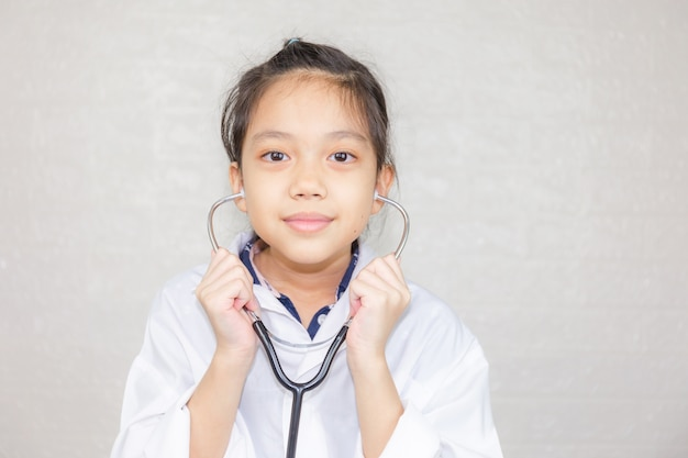 Dream careers concept, portrait of happy kid in doctor coat with stethoscope blurred background Premium Photo