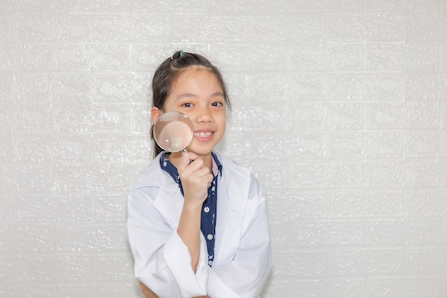 Dream careers concept, portrait of happy kid in science coat with magnifying glass on blurred background Premium Photo