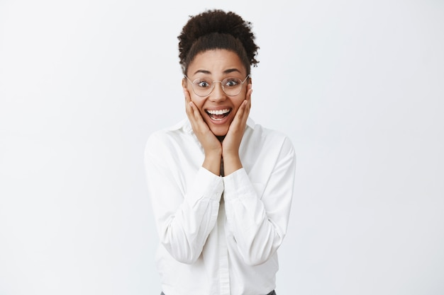 Dream come true. surprised happy and joyful attractive female entrepreneur in glasses and white shirt with dark skin, holding hands on cheeks and smiling broadly from amazement and happiness Free Photo