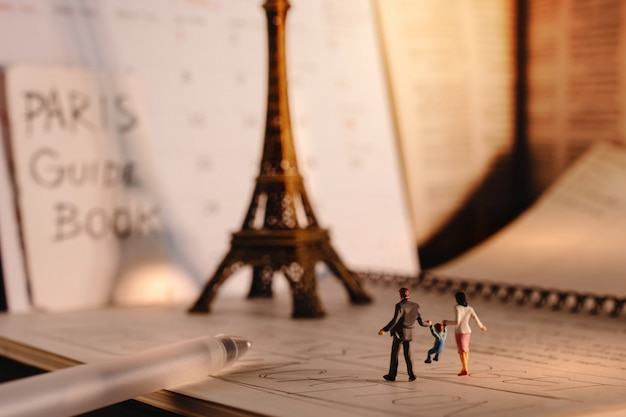 Dream destination for vacation. travel in paris, france. a miniature tourist family walking at the eiffel tower and calendar. warm tone. vintage style Premium Photo