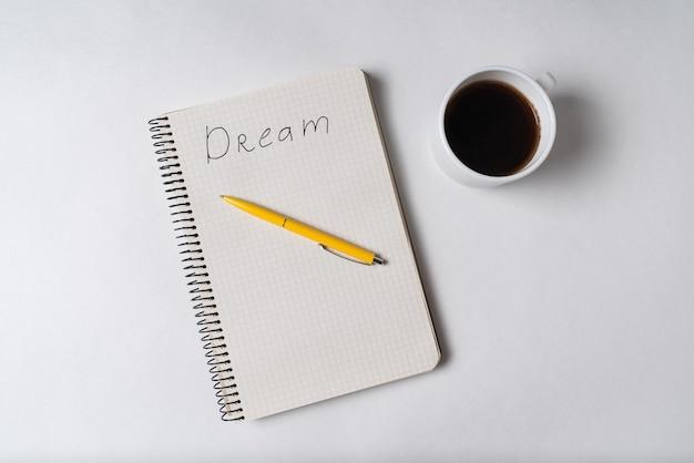 Вид сверху блокнот с надписью dream. ручка и чашка кофе. мотивационная заметка Premium Фотографии