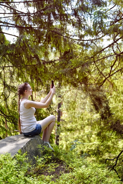 Dreaming beautiful girl sitting on a stone and making selfie on a smartphone surrounded by coniferous forest on a sunny day Premium Photo