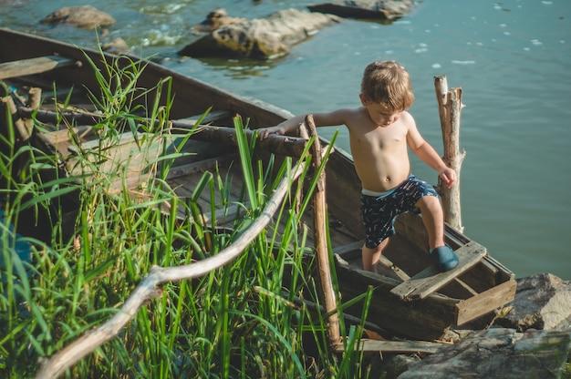 Мечтательный мальчик в старой лодке на берегу озера. милый маленький мальчик, сидящий в старой деревянной лодке на природе. Premium Фотографии