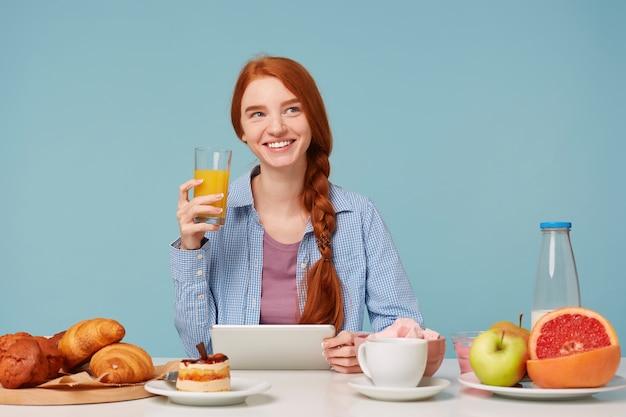 Мечтательно глядя в правый верхний угол, красивая улыбающаяся рыжеволосая женщина пьет апельсиновый сок Бесплатные Фотографии