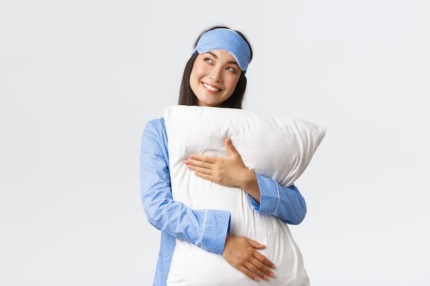 青いパジャマと眠っているマスクの夢のような美しいアジアの女の子は枕を抱いて、左上隅を見てベッドの中で何かを想像して、想像して、想像して笑って喜んでいます Premium写真