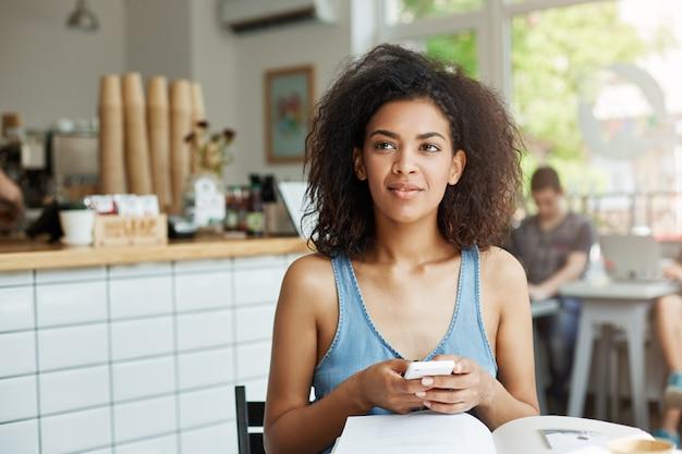 Мечтательный красивая женщина студент, сидя в кафе с книгами и журналами, улыбаясь, держа телефон мышления. Бесплатные Фотографии