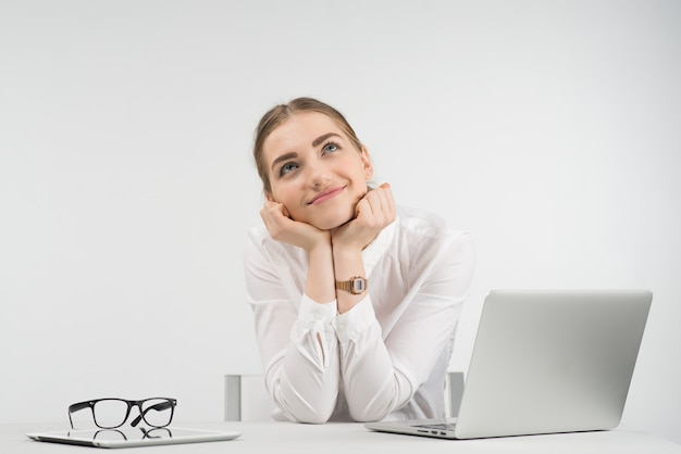 Dreamy  business woman sits next a laptop and looks up puting her head on the  her arms Premium Photo