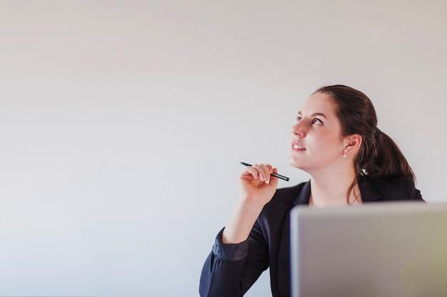 Dreamy businesswoman at laptop Free Photo