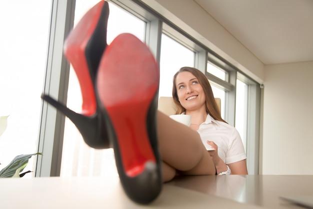 Мечтательная деловая женщина отдыхает на работе, пьет кофе, ноги на столе Бесплатные Фотографии