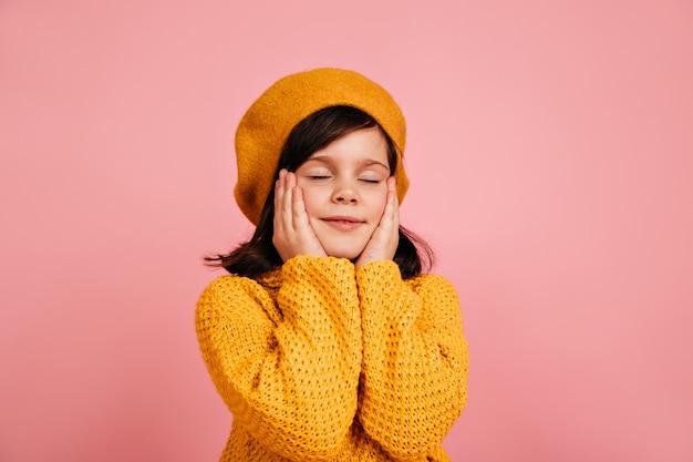 Мечтательный ребенок позирует с закрытыми глазами. беззаботный ребенок, изолированные на розовой стене. Бесплатные Фотографии