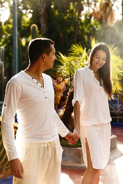 a8dcf1ac00ec Dreamy couple dressed in white closes walks around african city marrakesh in  a sunny evening Premium