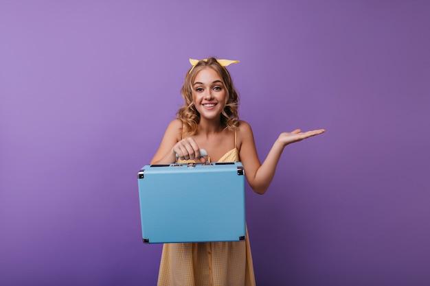 手荷物でポーズをとって黄色の衣装で夢のような巻き毛の少女。カメラに微笑んでスーツケースを持つdebonair女性モデルの肖像画。 無料写真