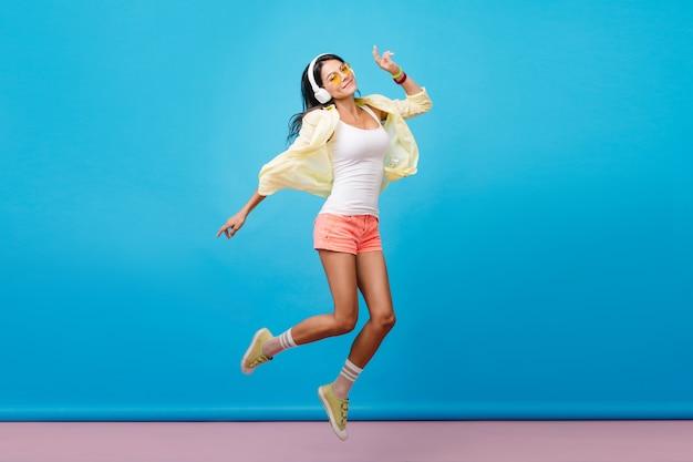 カジュアルなカラフルな服装で踊る夢のような黒髪のラテン女性。青い壁の部屋でジャンプする幸せな表情を持つロマンチックな若い女性の屋内写真。 無料写真