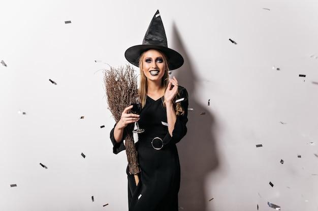 와인을 마시는 꿈꾸는 사악한 마녀. 할로윈 파티에서 웃 고 금발 머리를 가진 황홀 할 정도로 젊은 여자. 무료 사진