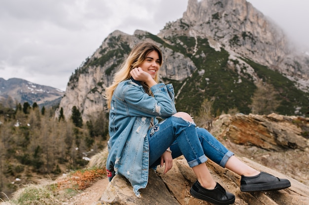 Dreamy fair-haired girl wearing denim attire resting on the rock after hard climbing and posing touching her face Free Photo