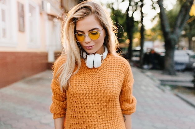 Giovane signora dai capelli biondi sognante in maglione giallo che osserva giù in piedi sulla sfocatura dello sfondo della strada Foto Gratuite