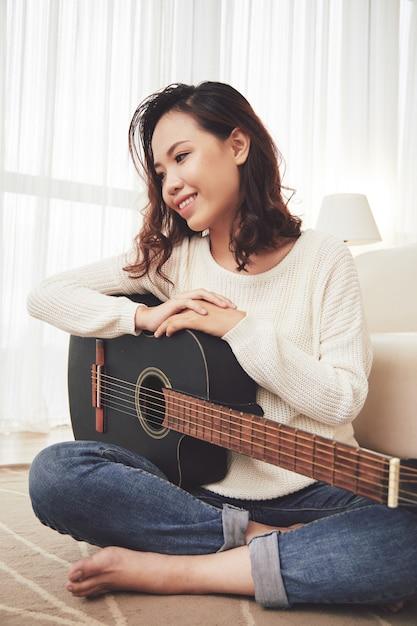 Dreamy girl enjoying playing guitar Free Photo