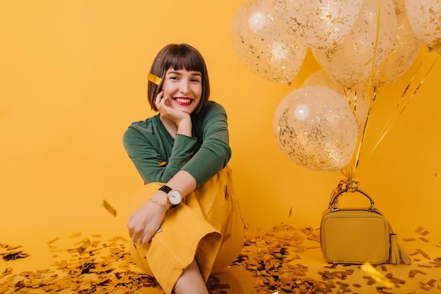 Ragazza sognante in seduta alla moda orologio da polso. ritratto di donna bruna romantica che gode del compleanno. Foto Gratuite