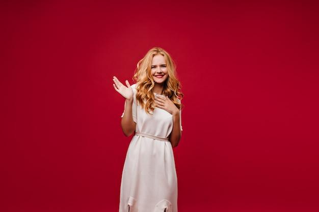 Мечтательная добродушная дама позирует в белом платье. восторженная длинноволосая девушка изолирована на красной стене. Бесплатные Фотографии