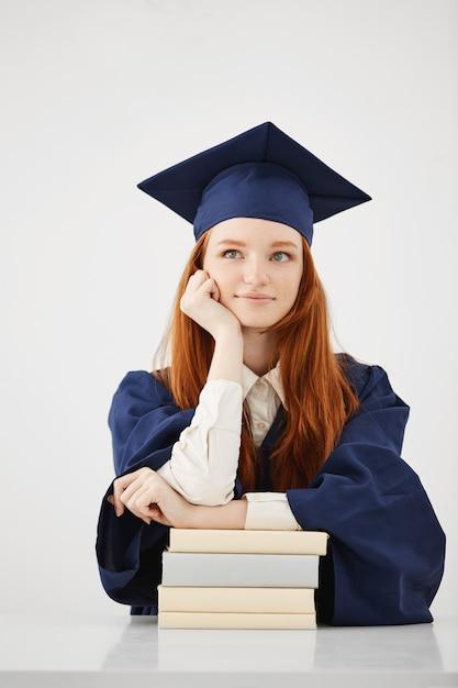 白い表面の上の本で座っている思考を笑っている夢のような大学院の女性 無料写真