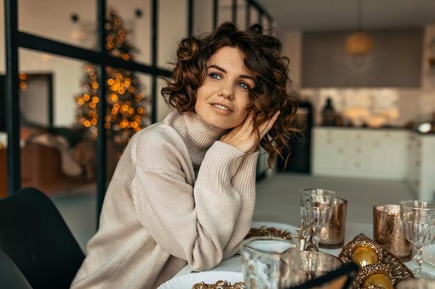 곱슬 헤어 스타일을 가진 꿈꾸는 행복한 여자는 크리스마스 트리 위에 크리스마스 테이블에 앉아 베이지 색 니트 스웨터를 입고 무료 사진
