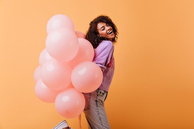 헬륨 풍선의 무리와 함께 춤을 캐주얼 복장에 꿈꾸는 아가씨. 생일 파티를 준비하는 착한 흑인 소녀. 무료 사진